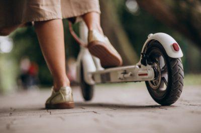 v-mujer-joven-equitacion-patineta-estacionamiento-pies-cicatrizarse_1303-15755